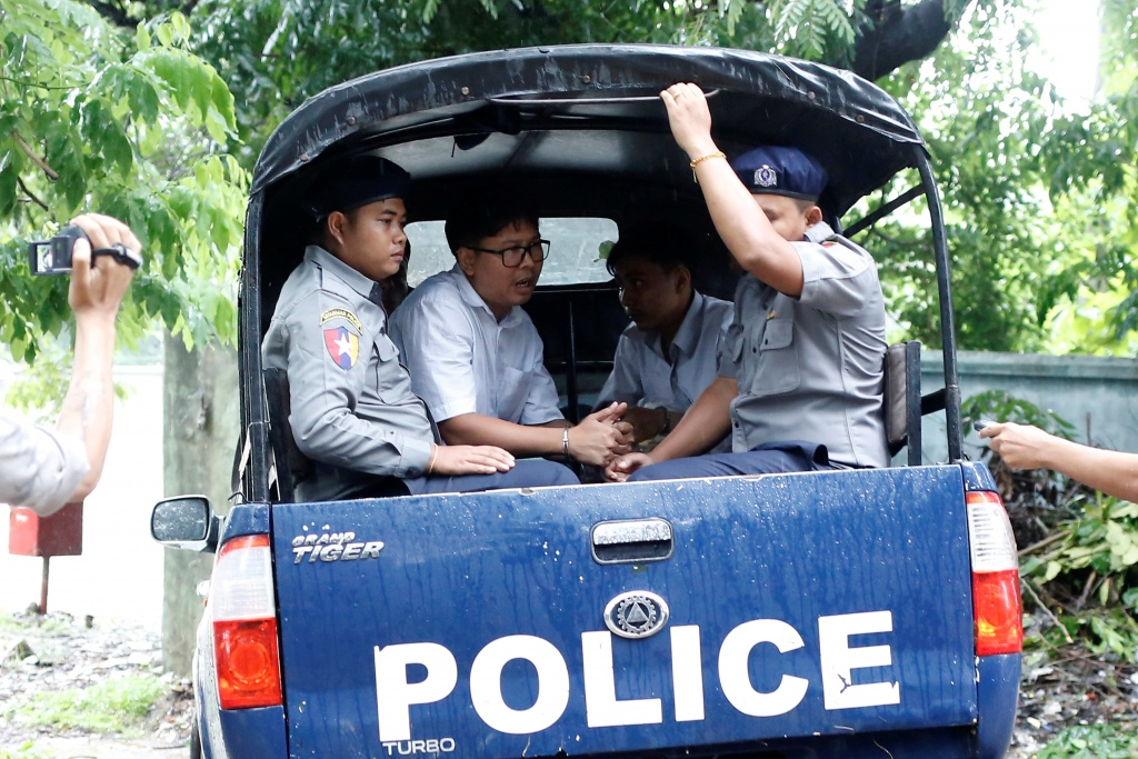 Detained Reuters journalists Wa Lone and Kyaw Soe Oo leave in a police vehicle after a court hearing in Yangon