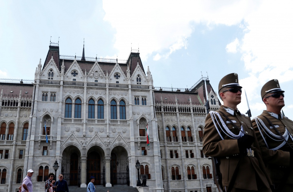 Two soldiers stand in front of the Hungarian Parliament building in Budapest