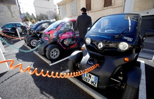 A man prepares to drive a Totem-Mobi electric car-sharing vehicle parked at a charging station in Marseille