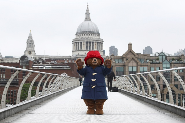 A performer wearing a Paddington Bear costume poses for photographers in front of St Paul's Cathedral in London