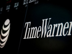 Logos and trading information for AT&T and Time Warner are displayed on a screen on the floor of the New York Stock Exchange