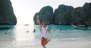 A tourist jumps as she pose for a photo at Maya Bay in Krabi province