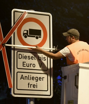 Traffic signs, which ban diesel cars are installed by workers at the Max-Brauer Allee in downtown Hamburg