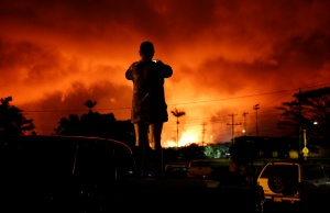 A woman takes a photo as lava lights up the sky above Pahoa