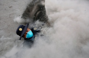 A police officer stumbles while running away from a new pyroclastic flow spewed by the Fuego volcano in the community of San Miguel Los Lotes in Escuintla