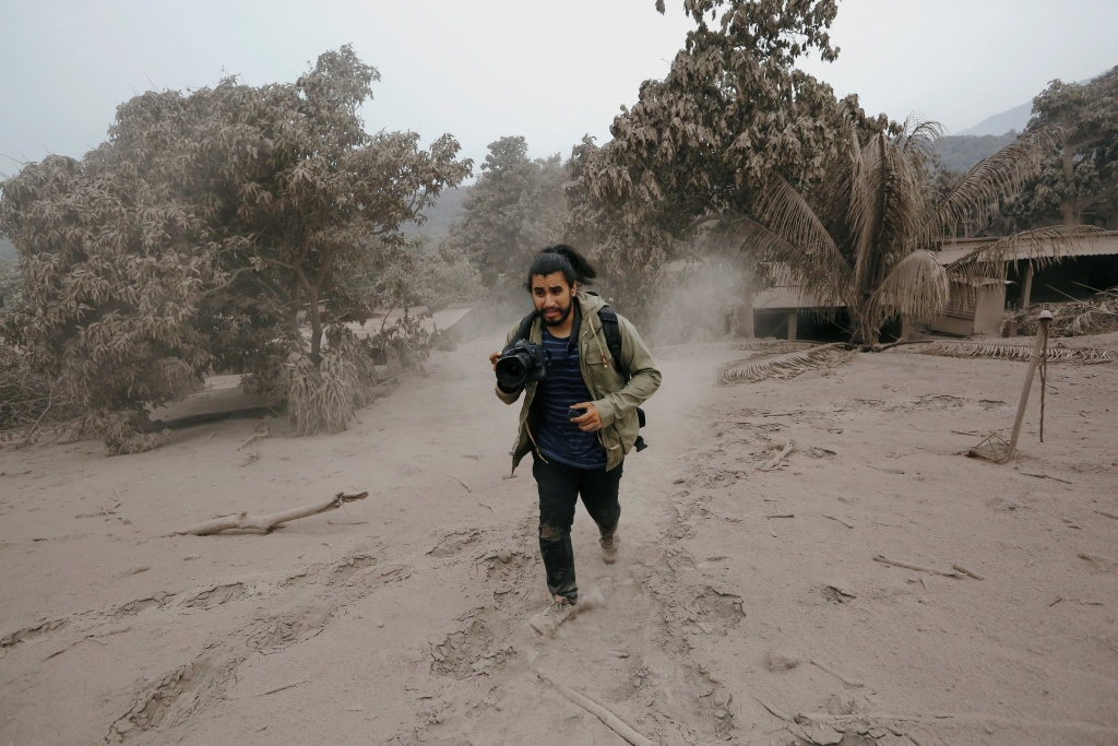 A photographer runs away from a new pyroclastic flow spewed by the Fuego volcano in the community of San Miguel Los Lotes in Escuintla