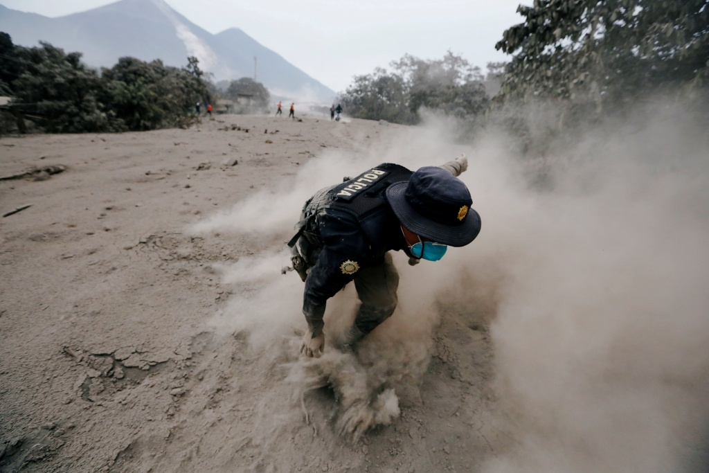 A police officer stumbles while running away after the Fuego volcano spew new pyroclastic flow in the community of San Miguel Los Lotes in Escuintla