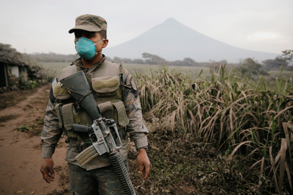 A soldier keeps watch at an area affected by an eruption from Fuego volcano in the community of San Miguel Los Lotes in Escuintla