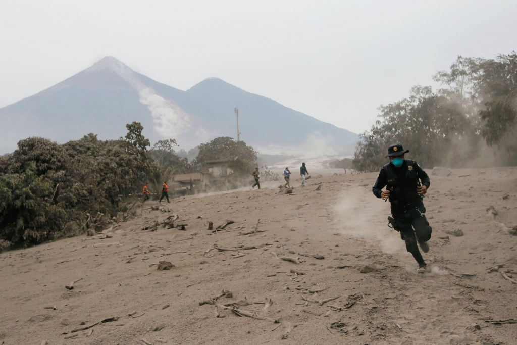 A police officer runs away from a new pyroclastic flow spewed by the Fuego volcano in the community of San Miguel Los Lotes in Escuintla