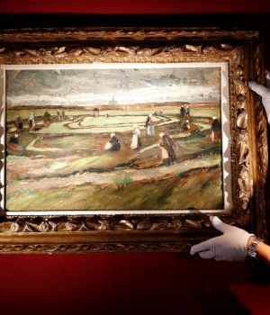 An Artcurial employee poses as he holds the painting «Raccommodeuses de filets dans les dunes, 1882» (Women Mending Nets in the Dunes) by Vincent Van Gogh during a preview for media at their auction house in Paris
