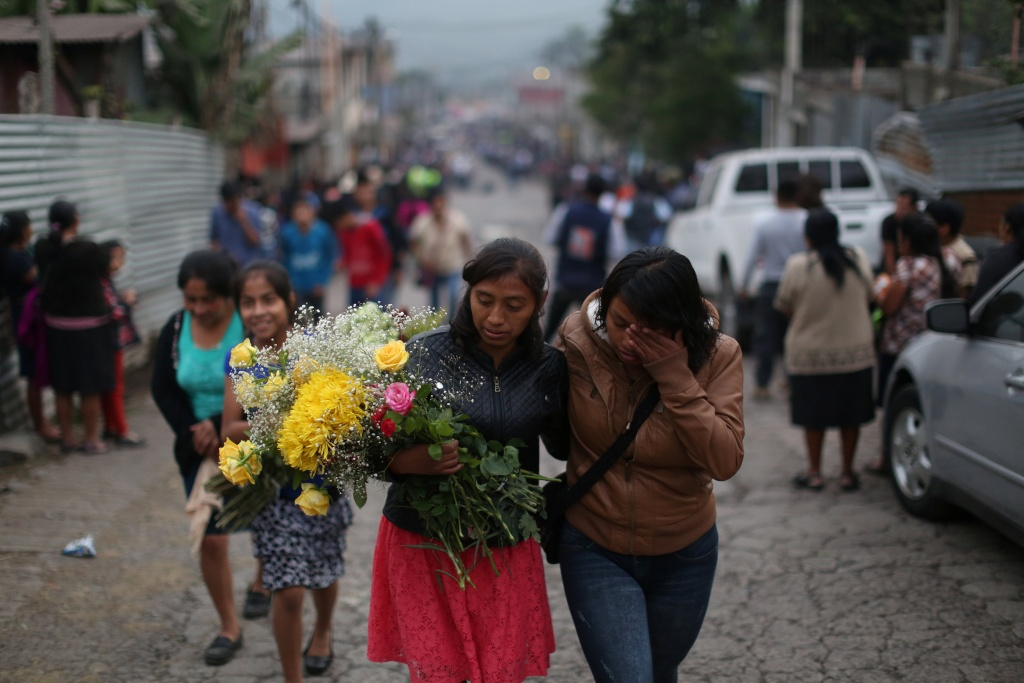 Women participate participate in the funeral of seven victims who died during the eruption of the Fuego volcano in Alotenango
