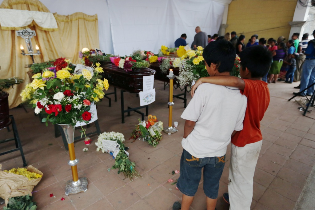 Children watch coffins of victims who died during the eruption of the Fuego volcano, during a wake at a plaza in Alotenango