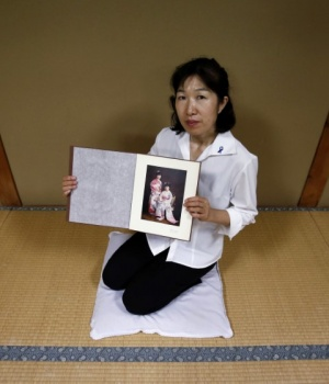 Misa Morimoto shows a photograph of her older sister and herself in 1984, during an interview with Reuters in Otsuki