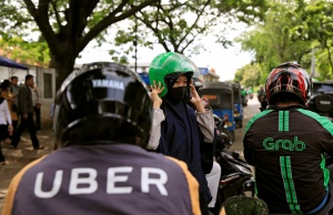 A passenger of Grab bike fixes her helmet next to Uber driver at Manggarai train station in Jakarta