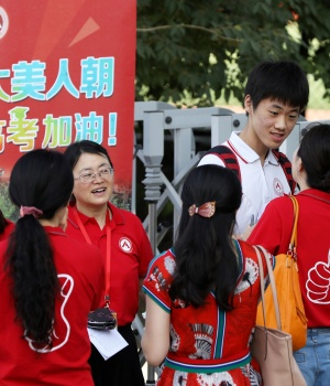"Teachers in red tee-shirts talk with a student before he enters the venue for the annual national college entrance examination, or ""gaokao"", in Beijing"