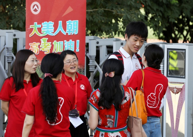 Teachers in red tee-shirts talk with a student before he enters the venue for the annual national college entrance examination, or