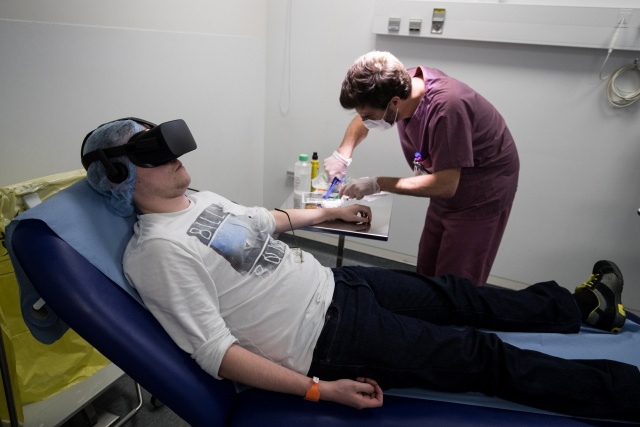 A nurse treats a patient wearing the 3D therapeutic virtual reality headset developped by Healthy Mind start-up, at the emergency department of the Saint-Joseph Hospital in Paris