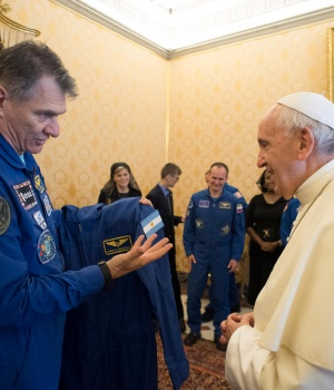 Pope Francis receives an astronaut suit from Italian astronaut Paolo Nespoli during a private meeting with crew members of the ISS 53 space mission at the Vatican