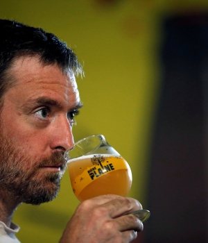 "A worker tastes the liquid from a mash tun during the beer brewing process at the ""La Plaine"" microbrewery in Marseille"