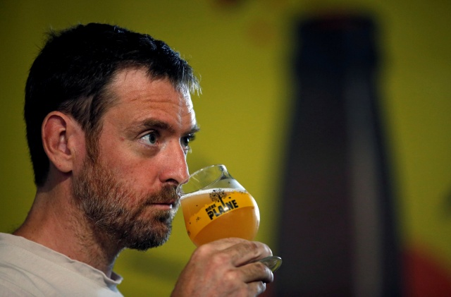A worker tastes the liquid from a mash tun during the beer brewing process at the