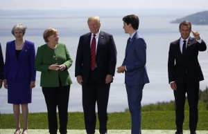 Leaders wave after posing for family photo at the G7 Summit in La Malbaie