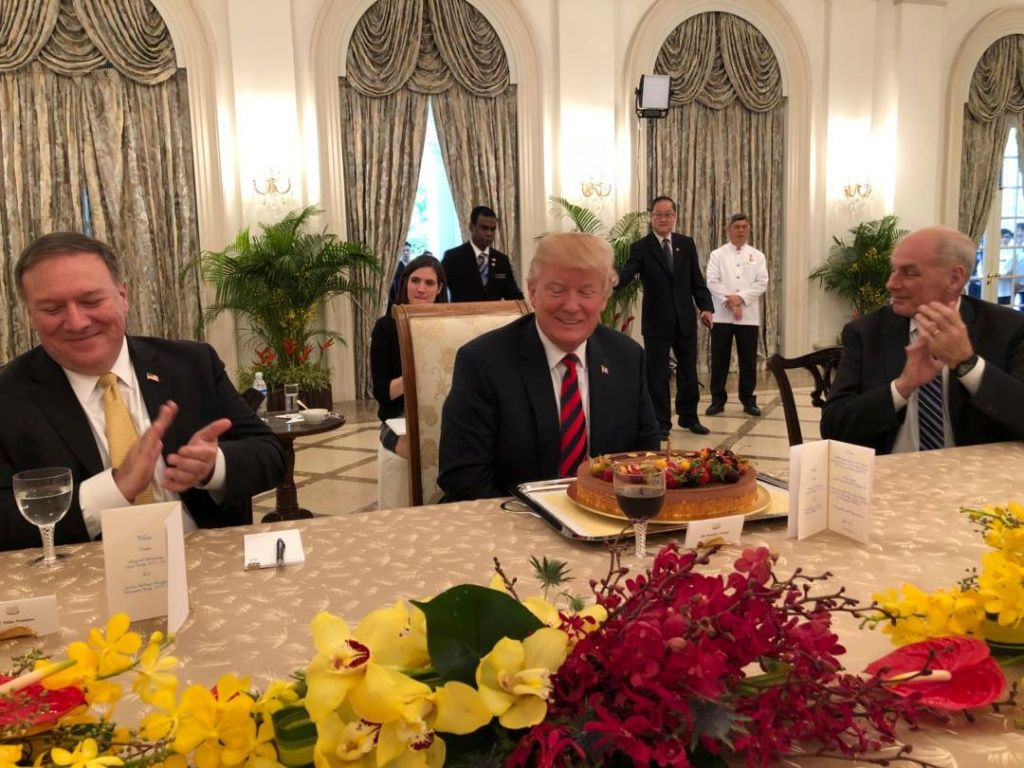 U.S. President Trump smiles in front of cake during advanced birthday celebration at meeting with Singapore's PM Lee in the Istana, Singapore