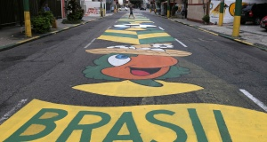 A man walks on a street painted in the colors of the Brazilian flag ahead of the 2018 World Cup, at Vila Isabel neighborhood in Rio de Janeiro