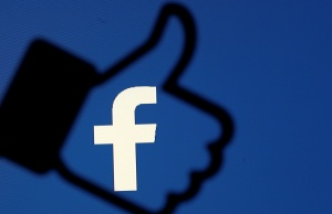 A 3D-printed Facebook like button is seen in front of the Facebook logo, in this illustration