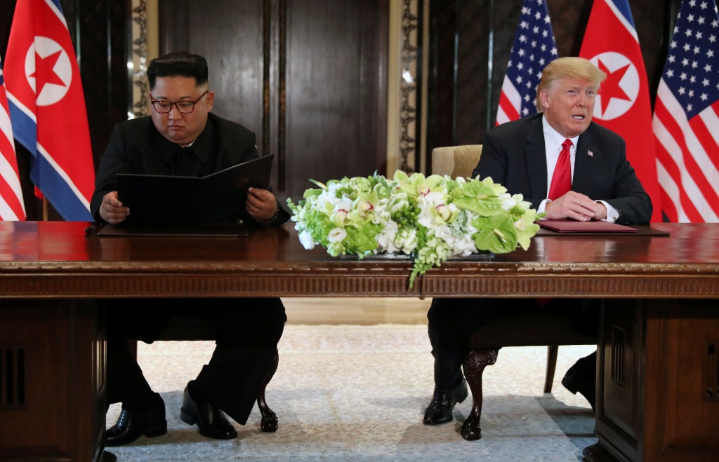 U.S. President Donald Trump speaks while North Korea's leader Kim Jong Un looks at the signed document, after their summit in Singapore