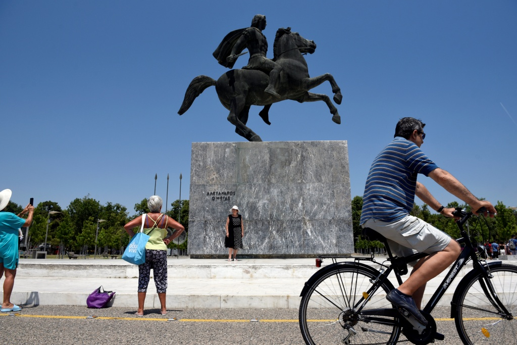 Tourists take pictures in front of a statue of Alexander the Great in the northern city of Thessaloniki