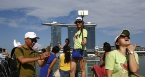 Tourists pose for photos with the Marina Bay Sands and the Merlion statue at a popular tourist spot along Marina Bay in Singapore