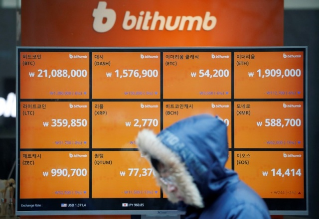 A man walks past an electric board showing exchange rates of various cryptocurrencies at Bithumb cryptocurrencies exchange in Seoul