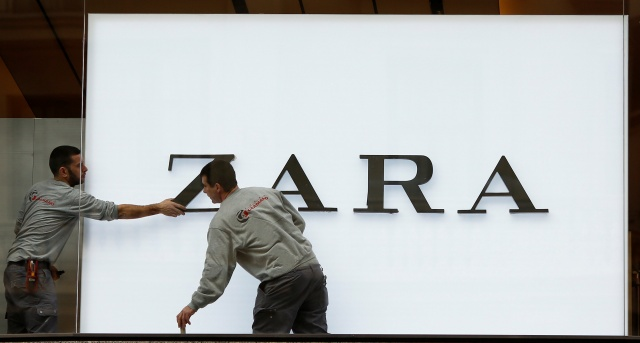 Workers put up the letters of the logo at a Zara store, an Inditex brand, in Madrid