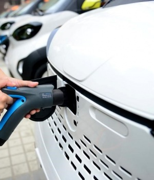 Staff member hooks up a charging cable to EV at a charging station in Liuzhou
