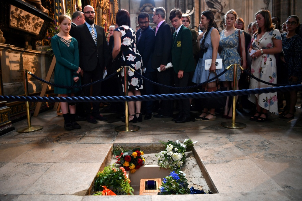 Members of the congregation file past the ashes of British scientist Stephen Hawking at the site of their interment in the nave of the Abbey church, during a memorial service at Westminster Abbey, in London