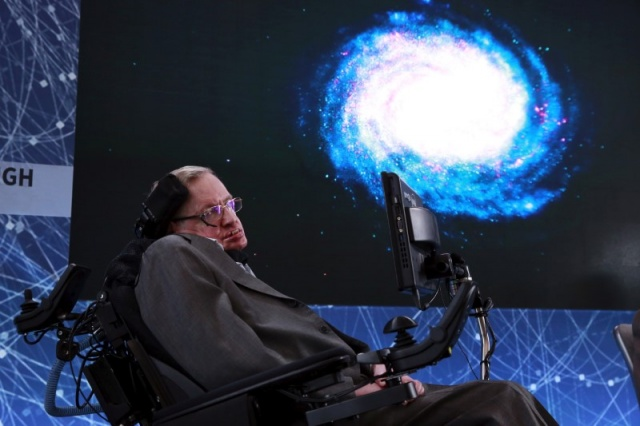 Physicist Stephen Hawking sits on stage during an announcement of the Breakthrough Starshot initiative with investor Yuri Milner in New York
