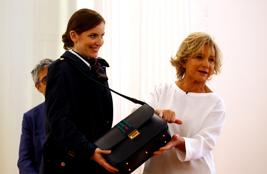 Italian designer Alberta Ferretti shows the details of a bag during the official presentation of Alitalia's new Alberta Ferretti-designed uniforms in Milan