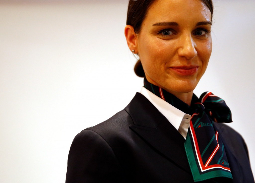 An Alitalia airline crew member poses with the new uniform during the official presentation of Alitalia's new Alberta Ferretti-designed uniforms in Milan