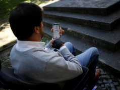 Wheelchair user Ricardo Teixeira demonstrates the phone app he developed to report accessibility infringements to authorities, while unable to proceed to the sidewalk, in Lisbon