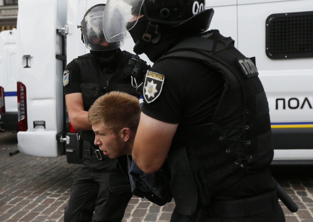 Riot police officers detain an anti-LGBT protesters during the Equality March in Kiev