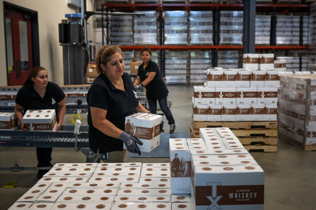 Employees move cases of whiskey at Firestone & Robertson in Forth Worth, Texas