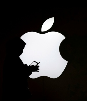 A woman looks at the screen of her mobile phone in front of an Apple logo outside its store in Shanghai