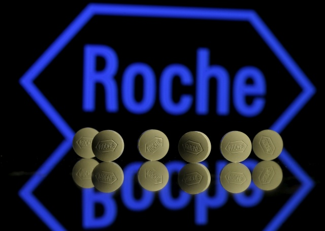 Roche tablets positioned in front of a displayed Roche logo