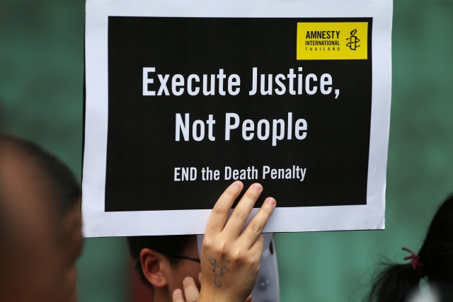 A demonstrator from Amnesty International holds a placard outside the Bang Kwang Central Prison to protest against the death penalty in Bangkok