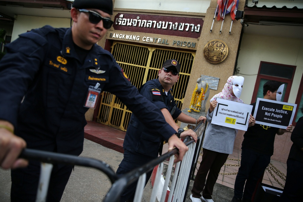 Prison wardens stand guard as demonstrators from Amnesty International hold placards outside the Bang Kwang Central Prison to protest against the death penalty in Bangkok