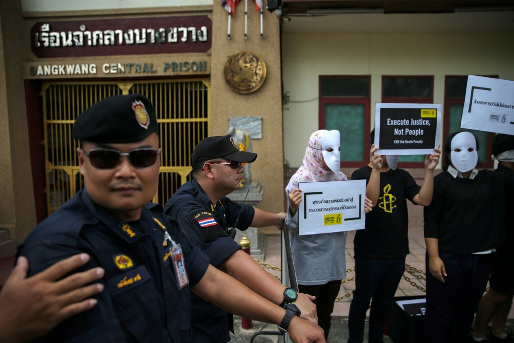 Prison wardens stand guard as demonstrators from Amnesty International hold placards outside the Bang Kwang Central Prison to protest against the death penalty in Bangkok, Thailand