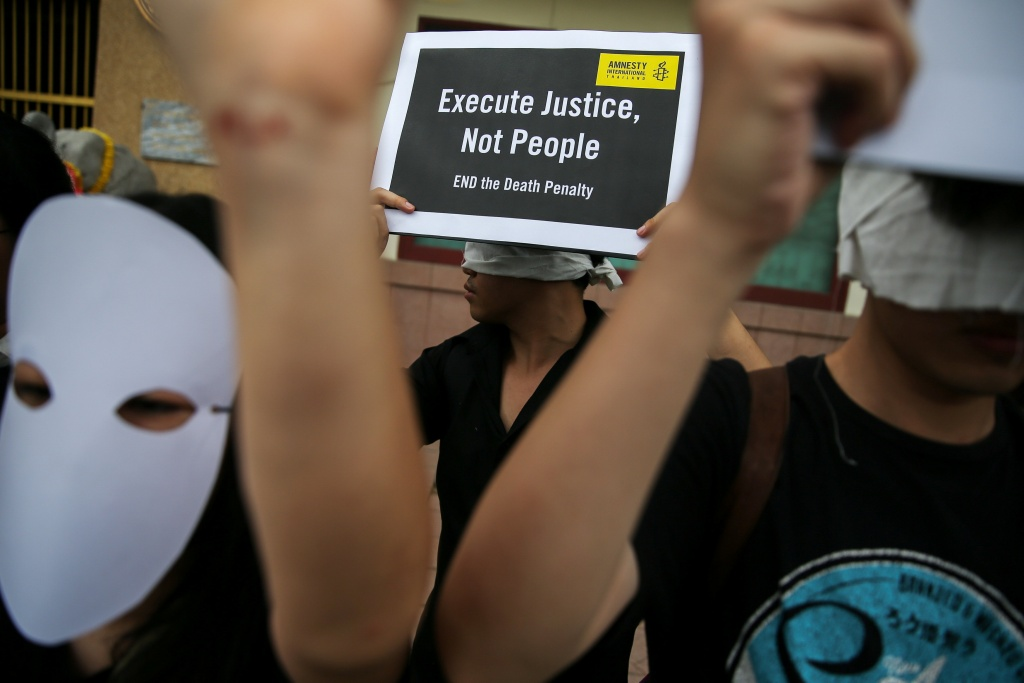 Demonstrators from Amnesty International hold placards outside the Bang Kwang Central Prison to protest against the death penalty in Bangkok, Thailand