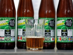 A sample of beer is seen with beer bottles at the Melody Brew brewery in Polevskoy
