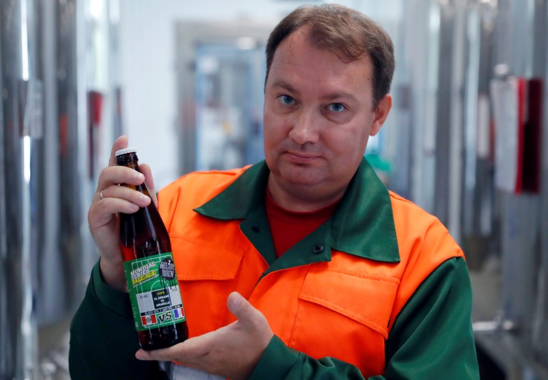 Chief brewer Alexei Saburov poses with a bottle of beer at the Melody Brew brewery in Polevskoy
