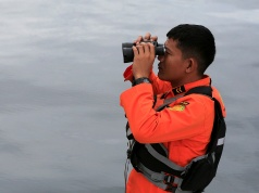 A rescue team member using binocular during operation to find missing passengers from a ferry accident at the Lake Toba in Simalungun